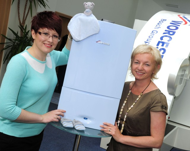 Rachel Cranny from Acorns Children's Hospice with Sue Pennington,Worcester, Bosch Group with the unique baby blue boiler being raffled to raise money for the charity